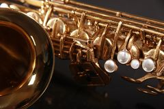 Part of sax. Part of shiny golden saxophone on black background Royalty Free Stock Photos
