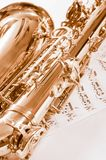Part of saxophone lying on the notes. Part of the saxophone lying on the notes Royalty Free Stock Photo