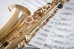 Part of saxophone lying on the notes Stock Images