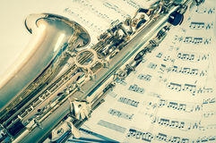 Part of saxophone lying on the notes. vintage style Royalty Free Stock Image