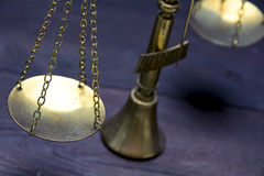 Part of scale or scales of brass on a dark wood, justice concept Stock Photos