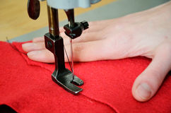 Part of sewing machine, red  woolen and female hand close up. ho Stock Photo
