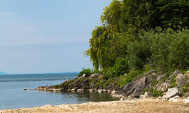 Part of small beach on Leman lake. Part of lake Leman coast with the beautiful green park, sand beach and many rocks. Lausanne Switzerland Stock Image