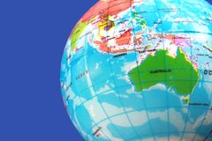 Part of a small globe showing Australia, the Indian Ocean and Southeast Asia. Part of a small globe on a blue background showing Australia, the Indian Ocean and stock photo