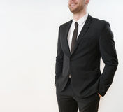 Part of smiling business man in black suit with hands in pockets Royalty Free Stock Images