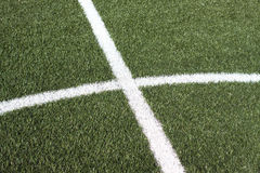 Part of a soccer field with green synthetic grass and white lines Stock Images