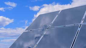 Part of a solar array located outdoors is mirroring clouds. 4K stock video