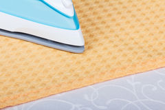 Part of steam iron, towel on abstract light gray background. Stock Photography