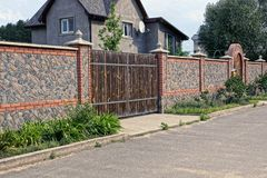 Part of the stone run and closed gates in the grass near a private house stock images