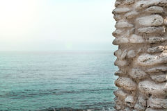 Part of the stone wall against the sea. Seascape Royalty Free Stock Image