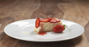 Part of strawberry cheesecake on plate on wood table Stock Photos