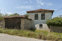 Part of street in the Paunovo village with old house, tree and fence, Sredna Gora mountain. Ihtiman, Bulgaria, Europe royalty free stock image