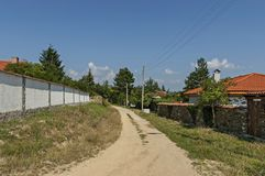 Part of street in the Paunovo village with old house, tree and fence, Sredna Gora mountain. Ihtiman, Bulgaria, Europe royalty free stock photo
