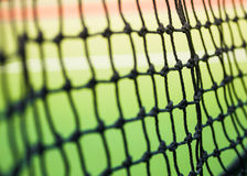 Part of tennis net. In green and red hard court Royalty Free Stock Photography