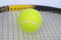 Part of tennis racquet with yellow ball clo. Part of tennis racquet with fluffy yellow ball closeup Stock Images