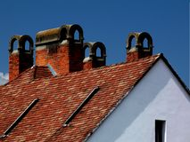 Part of clay tile roof structure and brick chimneys Stock Photo