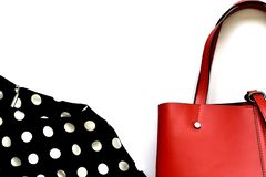 Part of trendy red women handbag or purse and polka dot black and white blouse stock photography
