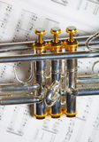 Part of trumpet. Close up part of silver B-flat trumpet on top of music sheet Royalty Free Stock Photos