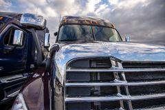 Part of two big rig semi trucks standing side by side on the parking lot. Front part of two professional commercial industrial delivery big rig long haul shiny royalty free stock image