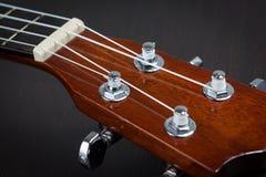 Part of ukulele hawaiian guitar. Haedstock of ukulele hawaiian guitar over dark background Stock Photo