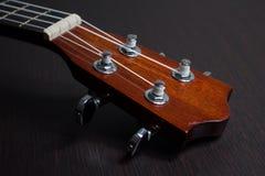 Part of ukulele hawaiian guitar. Headstock of ukulele hawaiian guitar over dark background Royalty Free Stock Images