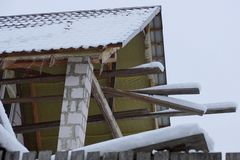 Part of an unfinished attic house with planks and tiles under white snow royalty free stock photos