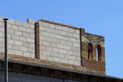 Part of an unfinished house made of gray and brown brick walls. Against a blue sky royalty free stock image