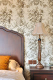 Part view of bedroom with flowery wallpaper Stock Images