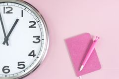 Part of wall clock with pink notepad and pen royalty free stock image