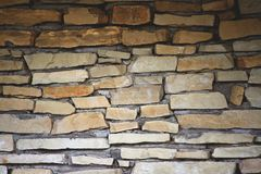 Part of the wall is made up of individual pieces of stones in cement. The dark upper part is gradually lighter down, yellow and brown shades royalty free stock photography