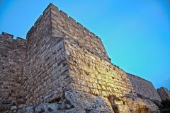Old Jerusalem City Wall at Dusk. Part of the wall of the old city of Jerusalem, just before sundown with artificial light painting the wall with orange from Royalty Free Stock Photo