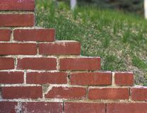 Part of the wall of red brick on the background of green lawn stock photography