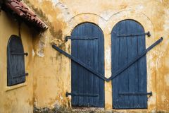 Part of wall with vintage closed windows. Detail of old colonial building in Sri lanka. Part of wall with vintage closed windows. Detail of old colonial building Royalty Free Stock Image
