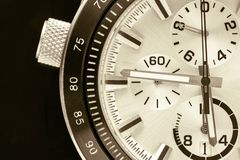 Part of the watch closeup. A half of a part of the men`s watch of chronographs closeup in black beige tone royalty free stock photography