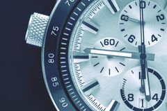 Part of the watch closeup. A half of a part of the men`s watch of chronographs closeup in black blue tone stock photography