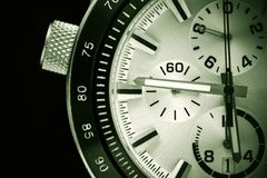 Part of the watch closeup. A half of a part of the men`s watch of chronographs closeup in black green tone stock photos