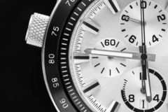 Part of the watch closeup. A half of a part of the men`s watch of chronographs closeup in black white tone stock image