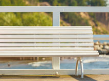 Part of white bench on pier. Rest and relax. Part of white wooden bench outdoor. Place for relaxation on pier near to the beach seaside Stock Image