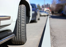 Part of a white car, a wing and a wheel on a blurred city background. In a parking lot Stock Images