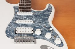 Part of white electric guitar, studio shoot.  2 x Single Coil and 1 x Humbucking. Black Pearl pickguard, Rosewood Fingerboard. Part of white electric guitar stock photos