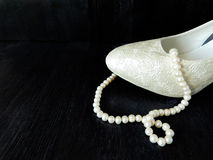 A part of white heel and pearl beads Royalty Free Stock Images