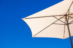 Part of white umbrella on background blue sky at Royalty Free Stock Images
