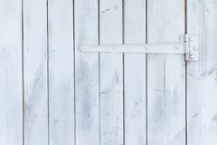 Part of the white wooden door with hinges.  Stock Photos