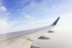 Traveling by plane. View from the window to the clouds and blue sky. Part of the wing of the airliner at altitude during the flight. Traveling by plane. View royalty free stock photo