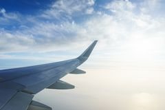 Traveling by plane. View from the window to the clouds and blue sky. Part of the wing of the airliner at altitude during the flight. Traveling by plane. View stock photos
