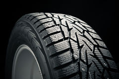 Part of winter tire. On black Stock Images