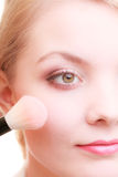 Part of woman face applying rouge blusher makeup detail. Stock Photos