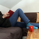 Part of woman reading in sofa Royalty Free Stock Photo