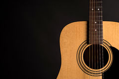 Part of a wooden acoustic guitar on the right side of the frame, on a black isolated background Royalty Free Stock Images