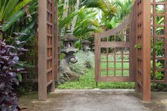 A part of wooden arbor with gate in ga.rden. Wooden arched entrance to the backyard. A part of wooden arbor with gate in garden. Wooden arched entrance to the Stock Photo